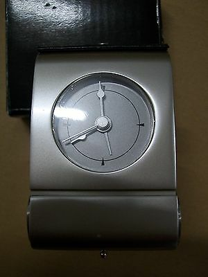 Art Deco style travel alarm clock, case opens to reveal face. Battery operated.