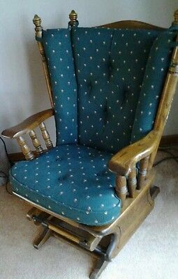 solid oak rocking chair   green padded seat and back.