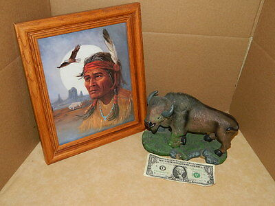 Black Buffalo Statue Mouth Open One Leg in Air on Grassy Plains and picture