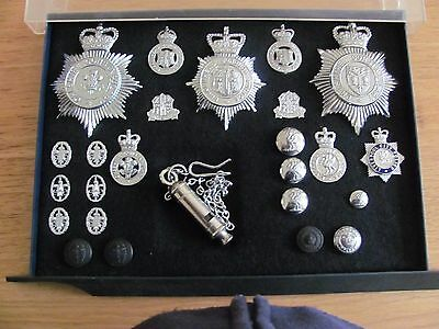 A collection of police badges,buttons,and a whistle