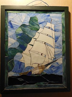 Stained glass mosaic of sailing ship, in wooden frame.