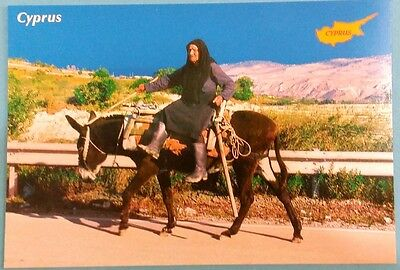 Cyprus postcard: Old woman on a donkey, unposted.