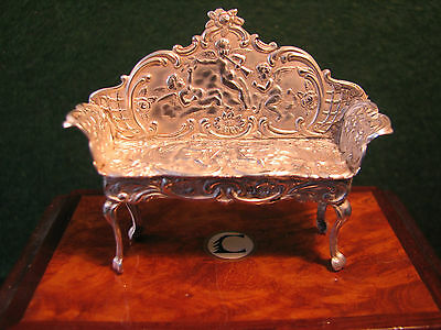 1901 Victorian silver miniature sofa chair decorated with cherubs & putti.
