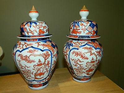 A pair of antique Meiji period Japanese pottery vases with lids Imari style