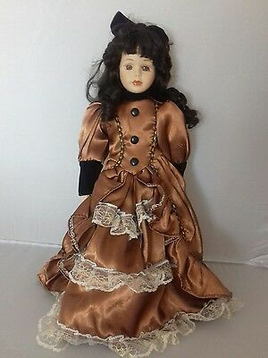 """16"""" Porcelain doll with dark hair and full length brown dress"""