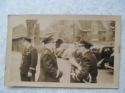 Four men in uniform,one with trumpet in car park,vintage cars old postcard