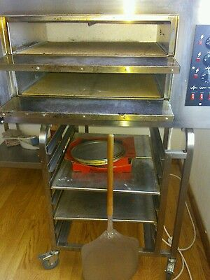 "pizza oven with stand.used good condition. Includes pizza trays 10""12""14"" ."