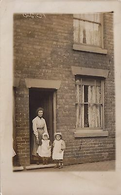 Mother & Two Children in front of the house Real Photograph Postcard.c.1910