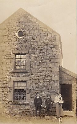 Family in front of their stone built house Real Photograph Postcard.c.1910