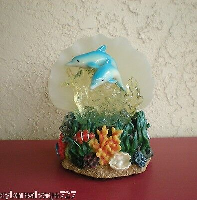 Two Dolphins On Wave And Coral Reef Lighted Colors Of The Sea Shell Background