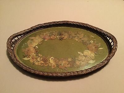 Antique wicker serving tray with pressed flowers under glass