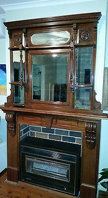 Intricate old wooden with mirrors fireplace mantle surround