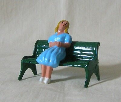 Girl in a dress sitting on park bench, Standard Gauge train layout, Reproduction