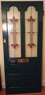 Solid timber front door painted dark green with stained glass windows