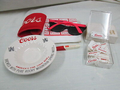 Coors Beer ashtray, koolie, sunglasses, scarf, clip-it, book marks.