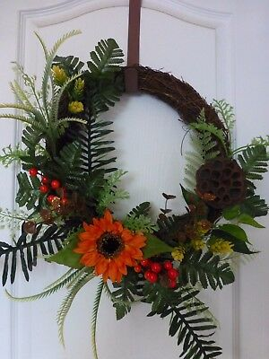 Fall wreath with orange sunflower and artificial greenery autumn colors