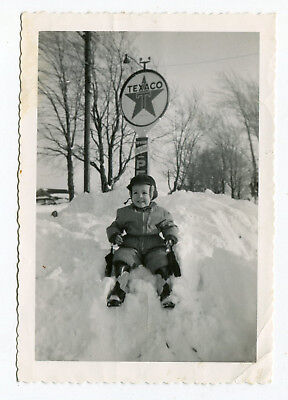 1950's Snapshot Photo Little Boy On Snow Bank Under Texaco Porcelain Banjo Sign