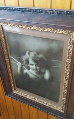 Antique oak framed print of cherub.1 of pair