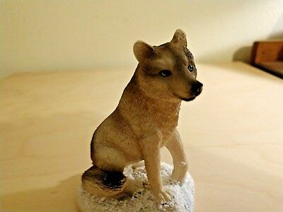 Seated Wolf Figurine On Snowy Ground