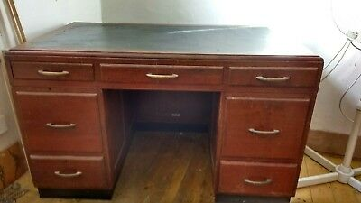 Antique leather topped desk and wooden filing cabinet.