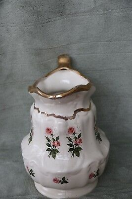 Porcelain water pitcher with gold trim and pink rises