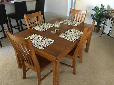 Solid oak dining room table with extension leaf and four chairs