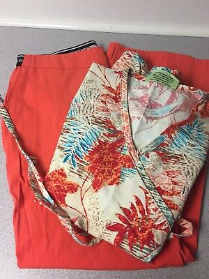 Lot of two medical scrubs color orange size top is small bottom is medium.