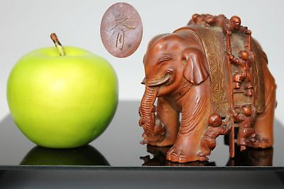 An antique Chinese carved wood figure of men climbing an elephant signed to base