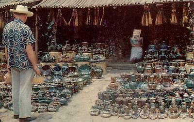 Mexico  -  A typical Mexican pottery market with a Tourist examining the wares