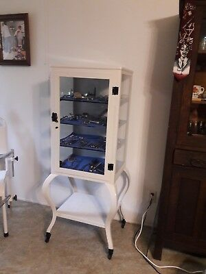 vintage steel medical/surgical instrument cabinet, glass shelves, on wheels. VGC