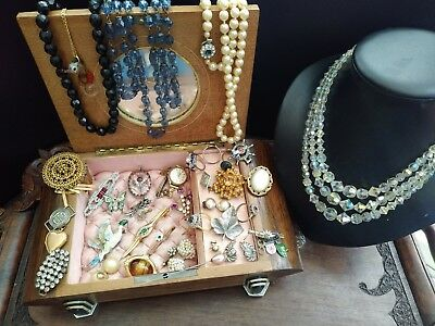 collection of vintage and art deco jewellery in a deco landor Swiss music box