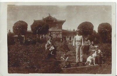 An Antique Russian Photo Postcard Of A Family Sitting Outside A House
