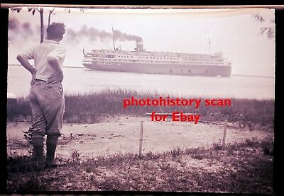 Person Watches Steam Ferry Steamship Boat go by Harsens Island Michigan Negative