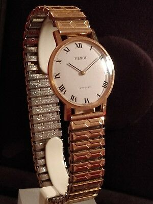 A 9ct gold gents Tissot stylist watch on a rolled gold bracelet working