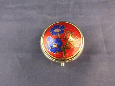 Small Metal Round Gold Coloured Pill Box with a Red and Blue Floral Design.