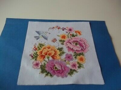 completed cross stitch floral design with a bird