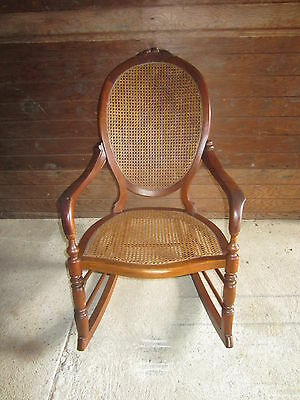Full sized antique walnut rocker excellent condition with a caned seat and back