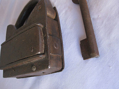 An old or antique Iron padlock lock trick puzzle with key
