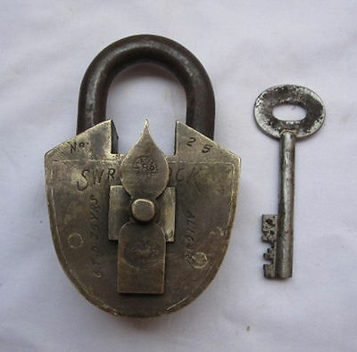 An old solid brass padlock trick or puzzle with key and a combination arrow