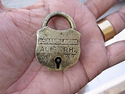 An old or antique solid brass small miniature padlock lock with key decorative