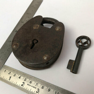 An old or antique iron padlock lock with key decorative oval shape.