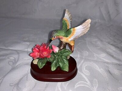 ceramic porcelain hummingbird figure collectable with trio of red  flowers.
