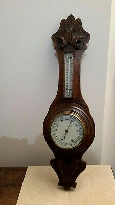 A carved oak cased barometer with detachable thermometer