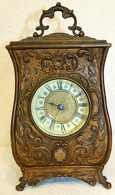 Antique metal alarm clock with small medallions applied with women's faces