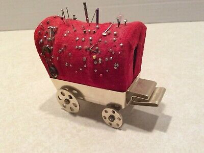 Vintage metal covered wagon pin cushion/tape measure