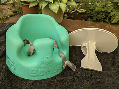 Green Bumbo seat with straps, tray, and box