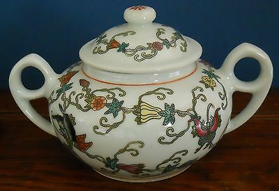 A two handled lidded pot in hand coloured ceramics butterfly and flower design