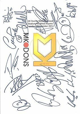 An A4 white card with the MK Dons Badge. Signed by 17 players on 28.10.14.