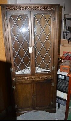 A late 20th Century stained oak corner display cabinet,
