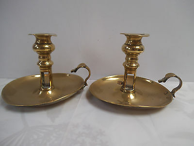 A pair of vintage brass chamber sticks with pusher